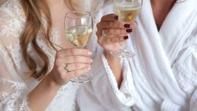 Two glasses of champagne in the hands of the girls. Two girls in dressing gowns with champagne in hands, close-up stock video footage