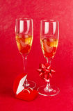 Two glasses with champagne and jewelry box on red Royalty Free Stock Images