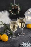 Two glasses with champagne and mandarins at black background royalty free stock photos