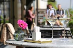 Two glasses of champagne, napkins and flower on a table in street cafe. Street cafe, table set in a restaurant outdoor, romantic meal, elegant setting for royalty free stock photo