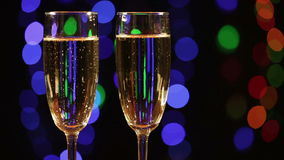 Two glasses with champagne over black. Two glasses with champagne appear from blur on black background with flashing lights stock video