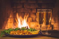 Two glasses with champagne and a plate with shrimps, lemon and greens on a wooden table against the background of a stock photography