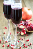Two glasses of champagne with pomegranate seeds Stock Photography