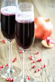 Two glasses of champagne with pomegranate seeds Royalty Free Stock Photos