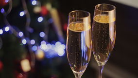 Two glasses of champagne ready for christmas celebration, on red background stock video footage