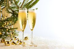 Two glasses of champagne ready to bring New Year on Christmas tree background. With text space stock photos