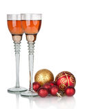 Two glasses of champagne with red Christmas ball