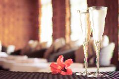 Two glasses of champagne with red flower in a spa lounge. Spa time concept. Spa lounge area. Glitch effect, colorful disruptive. Two glasses of champagne with royalty free stock images