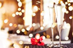 Two glasses of champagne with red flower in a spa lounge. Spa time concept. Spa lounge area. . Bold festive bokeh stock images