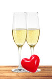 Two glasses of champagne and red heart on table isolated on whit Royalty Free Stock Photo