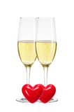 Two glasses of champagne and red hearts isolated on white Royalty Free Stock Photo