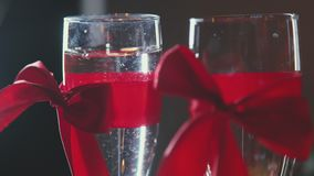 Two glasses of champagne with red ribbon. The 14th of February. stock video