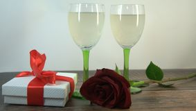 Two glasses of champagne, red rose and gift box on a wooden table royalty free stock photography