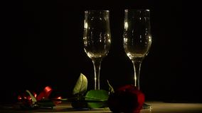 Glasses and rose on a black background. Two glasses for champagne and a red rose spinning on the presentation table stock footage