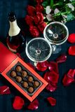 Two glasses of champagne, red roses, petals and chocolates on a black background stock photos