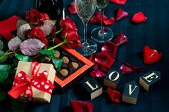 Two glasses of champagne, red roses, petals, gift box with red ribbon, chocolates and wooden love words on a black background royalty free stock photos