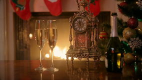 Two glasses of champagne and retro clock in front of burning fireplace at house. Concept of celebrating Christmas. Glasses of champagne and retro clock in front stock footage