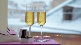 Two glasses of champagne, ring in box and note with heart in winter stock video footage