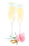 Two glasses of champagne, roses and rings. On a white background Royalty Free Stock Photo