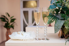 Two glasses with champagne and stand for rings Stock Photography