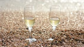 Two glasses of champagne stand on the sand with small shells by the sea, in the background waves wash the shore. Two glasses of champagne stand on sand with stock video