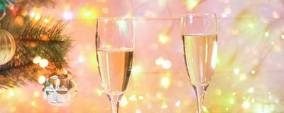 Two glasses of champagne stand on a white wooden table on the background of a New Year tree and garlands. Christmas bokeh. Two glasses of champagne stand on a royalty free stock photography