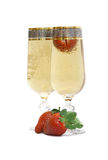 Two glasses with champagne and a strawberry. Two glasses with the champagne, decorated with a strawberry. Champagne and a strawberry on a white background Royalty Free Stock Photography
