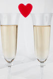 Two glasses with champagne and symbolic heart Stock Photos