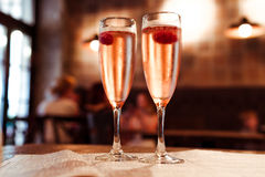 Two glasses of champagne on a table in a cafe. Two glasses of champagne with raspberry on a table in a cafe Royalty Free Stock Photo