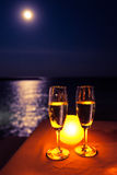 Two glasses of champagne on the table with candle near the sea under moon light. Romantic scene. Two glasses of champagne on the table with candle near the sea Royalty Free Stock Images
