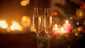 Two glasses of champagne on table in front of burning fireplace at Christmas eve. Two glasses of champagne on table in front of burning fireplace at Christmas stock footage