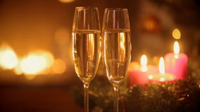 Two glasses of champagne on table in front of burning fireplace at Christmas eve. stock video