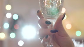 Two glasses with champagne toasting over holiday blinking background. Slowly stock video