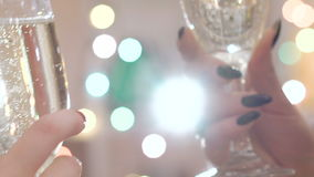 Two glasses with champagne toasting over holiday bokeh blinking background. Two glases with sparkling champagne toasting over holiday bokeh blinking background stock footage