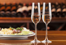 Two glasses of champagne with a tray of cheese Royalty Free Stock Photography