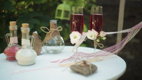 Two glasses with champagne and wedding attributes to the ceremony. In the park stock video footage