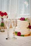 Two glasses of champagne and wedding cake on the table Stock Photos