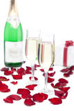 Two glasses of champagne on white backgro. Two glasses of champagne, gift box, rose petals on a white background stock photos