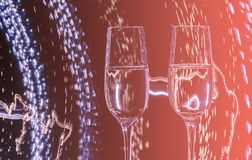 Two glasses of champagne wine on a background of abstract colored lights in motion in the natural color of the living coral. The color of the year 2019 stock image