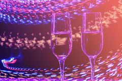 Two glasses of champagne wine on a background of abstract colored lights in motion in the natural color of the living coral. The color of the year 2019 royalty free stock photography