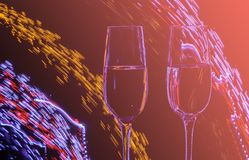 Two glasses of champagne wine on a background of abstract colored lights in motion in the natural color of the living coral. The color of the year 2019 royalty free stock photo
