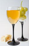 Two glasses of champagne, wine, cheese and grapes Royalty Free Stock Photos