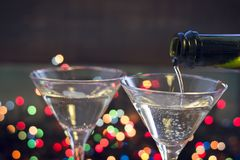 Two glasses of champaign. Close up. Two glasses of champaign on a dark bokeh background. Champaign is being poured into a glass from a bottle. Close up Royalty Free Stock Image