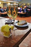 Two glasses of champaign and food. Still life. Color photo. Blurred figures of people at background royalty free stock photo