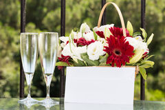 Two glasses of champange and flower basket with plain envelope Royalty Free Stock Photography