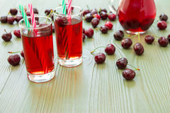 Two glasses of cherry juice and some empty space. Left 2 glasses of juice, green straws, scattered cherries, jar of cherry juice, on right empty space for text Royalty Free Stock Images