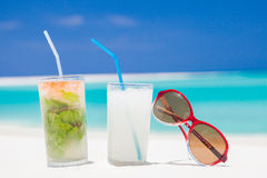 Two glasses of chilled cocktail mohito pina colada and sunglasses on a sand beach Royalty Free Stock Image
