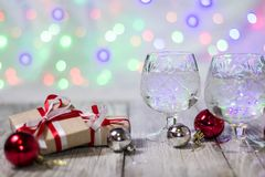 Two glasses of christmas champagne with gift boxes and balls decorations against light bokeh background.  Royalty Free Stock Images