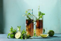 Cuba libre cocktail. Two Glasses of classic Cuba libre cocktail with lime, mint, crushed ice and cola, served with ingredients above and retro cocktail tubes Stock Photo