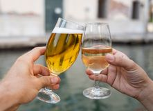 Two glasses click toasting cheers of couple celebrating holidays. Two glasses of beer and wine, couple drinking by the canal in Venice romantic celebration of royalty free stock photo